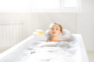 An Attractive girl relaxing in bath on light background